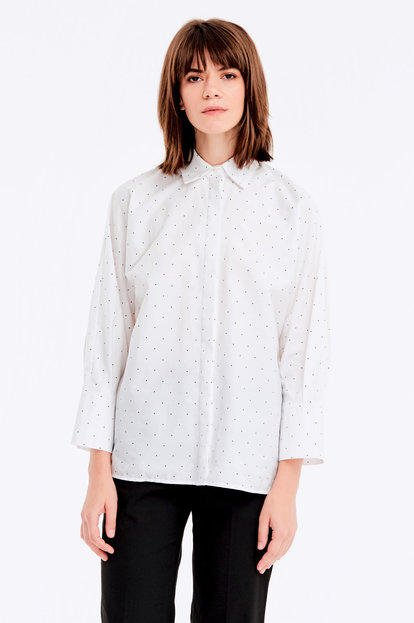 Loose-fitting white shirt with a black polka dot print and a concealed placket